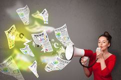 Girl yelling into loudspeaker and newspapers fly out Stock Image