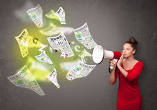Girl yelling into loudspeaker and newspapers fly out Royalty Free Stock Image