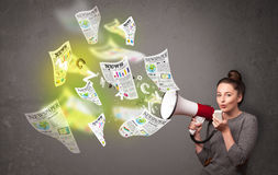 Girl yelling into loudspeaker and newspapers fly out Royalty Free Stock Photography