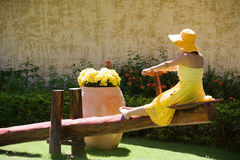 Girl in yellow. Gown swings on seesaw Royalty Free Stock Photography