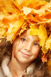 Girl with yellow autumn leaves on her head Stock Images