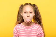 Girl sticking tongue out cute antics frolicking. Girl on yellow background sticking tongue out. cute antics and frolicking concept stock image