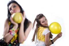 Girl with yellow balloon and girl with fruit Royalty Free Stock Photography