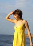 Girl in yellow on a bank of the river Royalty Free Stock Image