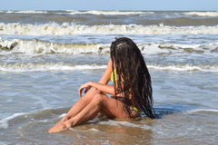 The girl in a yellow bathing suit on the beach. Girl with black hair sitting in sea water head bowed. Royalty Free Stock Photography