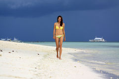 Girl in yellow bikini walking on the white beach under the storm sky Stock Photography