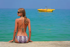 A girl and yellow boat. Beautiful girl sit on pier. Beach, Crete, Greece Stock Photos