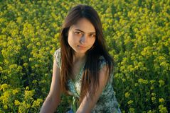 Girl on a yellow canola field Stock Photos