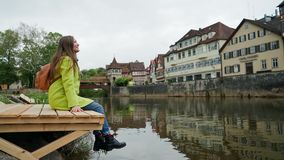 Girl in yellow coat with backpack sitting dangling on a wooden pier near water and looking at traditional german half. Timbered houses. Schwabisch Hall. Germany stock footage
