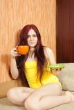 Girl in yellow with cup Stock Images