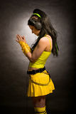 Girl in yellow - cybergoth style. Praying pose, with headphones on Stock Photo