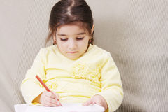 Girl in yellow drawing Stock Images