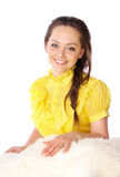 Girl in a yellow dress on fur clothing Royalty Free Stock Images
