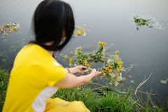 A girl in a yellow dress is holding a wreath of wild flowers. A girl in a yellow dress launches a wreath of wild flowers along the river Royalty Free Stock Image