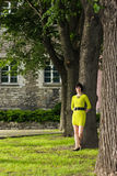 Girl in yellow dress leans on a tree in a park Stock Image