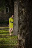 Girl in yellow dress leans on a tree in a park stock photography
