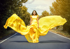 Girl in a yellow dress on road Royalty Free Stock Image