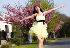 Girl in a yellow dress running down the avenue Stock Images