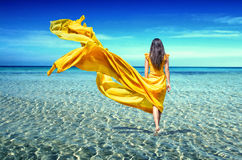Girl in a yellow dress in sea Royalty Free Stock Photography