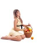 Girl in yellow dress sitting beside fruit basket stock images
