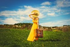 Girl in yellow dress and suitcase on mountain meadow with dandelions royalty free stock photos