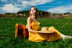 Girl in yellow dress and suitcase sitting on mountain meadow with dandelions royalty free stock image