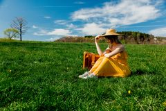Girl in yellow dress and suitcase sitting on mountain meadow with dandelions royalty free stock images