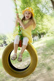 Girl in yellow dress on tire swing royalty free stock photo