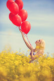 Girl in yellow field letting go of a bunch of balloons Royalty Free Stock Photo