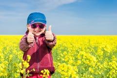 Girl in yellow field of rape Stock Photos