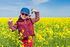 Girl in yellow field of rape Royalty Free Stock Image