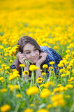 Girl in yellow flowers Stock Images