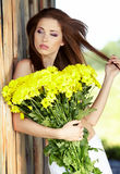 Girl with yellow flowers smiling Stock Images