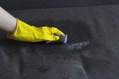 Girl in yellow gloves cleans the sofa, close-up sofa stock photo