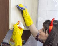 A girl in yellow gloves washes the locker in the kitchen, close-up royalty free stock image
