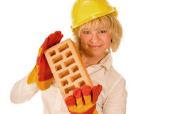 Girl in yellow hard hat. With brick Royalty Free Stock Photography