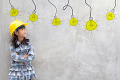 Girl in yellow helmet with light bulb ideas. Smiling little girl in yellow helmet with light bulb ideas Royalty Free Stock Photos