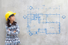 Girl in yellow helmet showing blueprint drawing on wall royalty free stock image
