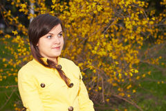 Girl in a yellow jacket. Young girl in a yellow jacket near an autumn bush Royalty Free Stock Photography