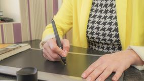 A girl in a yellow jacket draws on the tablet. At work vector illustration