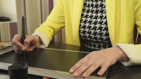 A girl in a yellow jacket draws on the tablet. stock footage