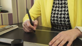 A girl in a yellow jacket draws on the tablet. stock video footage