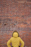 The girl in the yellow jacket looking at a brick wall. Girl in a yellow jacket looking at a brick wall Royalty Free Stock Photos