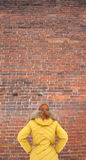 The girl in the yellow jacket looking at a brick wall. Girl in a yellow jacket looking at a brick wall Stock Photography