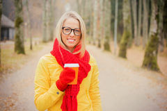 Girl in yellow jacket and red scarf having coffee Royalty Free Stock Photography