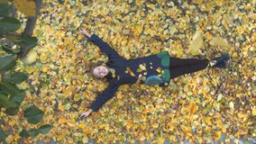 The girl among the yellow leafs. Slow motion. Top view. A young cheerful girl lies on the leaves. She closed her eyes and smiled. Leaves fall on the girl stock footage