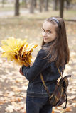 Girl and yellow leaves. At autumn. Bag on back Royalty Free Stock Photos