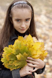 Girl and yellow leaves. At autumn Stock Photo