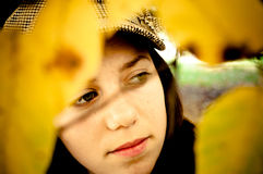 Girl through yellow leaves Stock Images