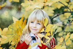 Girl with yellow leaves in arms. In autumn park Stock Image
